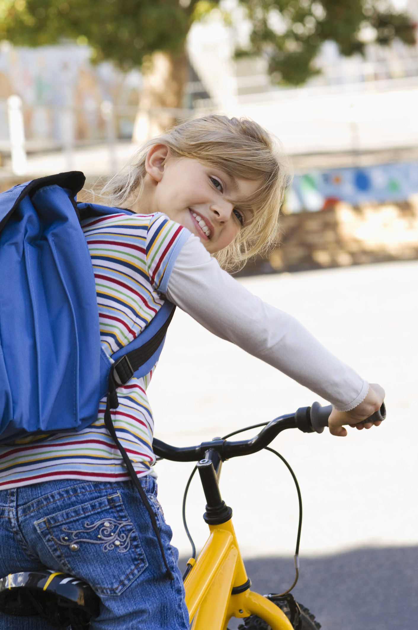 Girl riding bicycle with backpack
